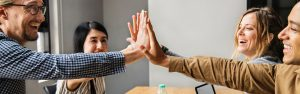 Four adults high-fiving because of agreement