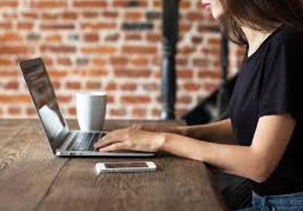 Millennial in coffee shop working on laptop